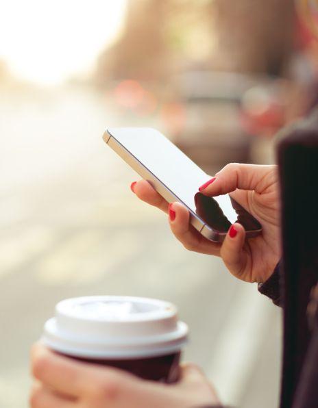 Dame taster på telefon og drikker kaffe
