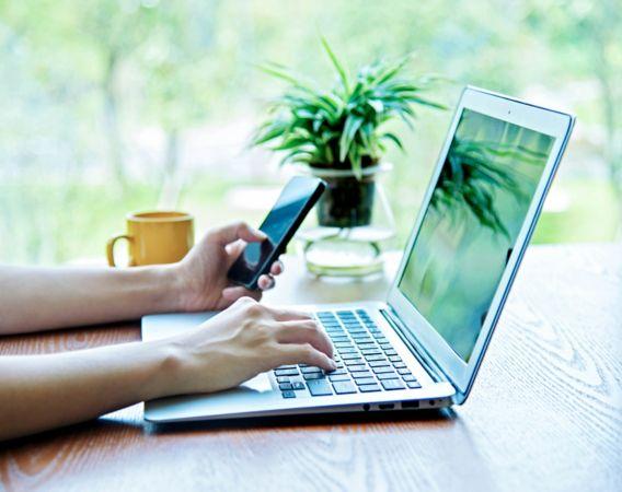 Bilde av en person bruker laptop og mobil