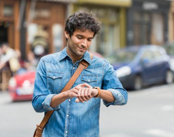 Bilde av kjekk mann som ser på sin egen klokke