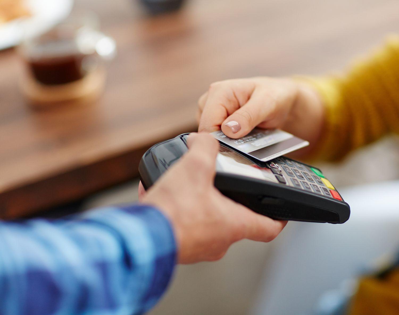 Bilde av et kredittkort som blir brukt på en bankterminal.