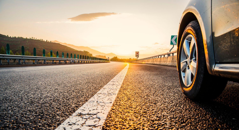 Bilde av bil og vei i solnedgang.