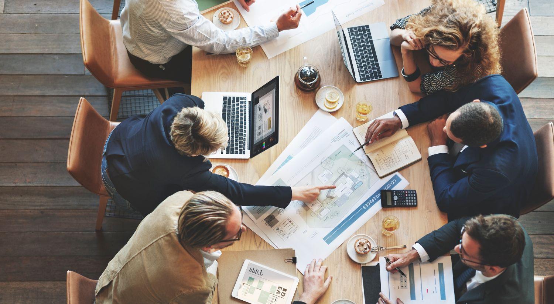 Mennesker sitter ved et bord og jobber sammen. Foto.