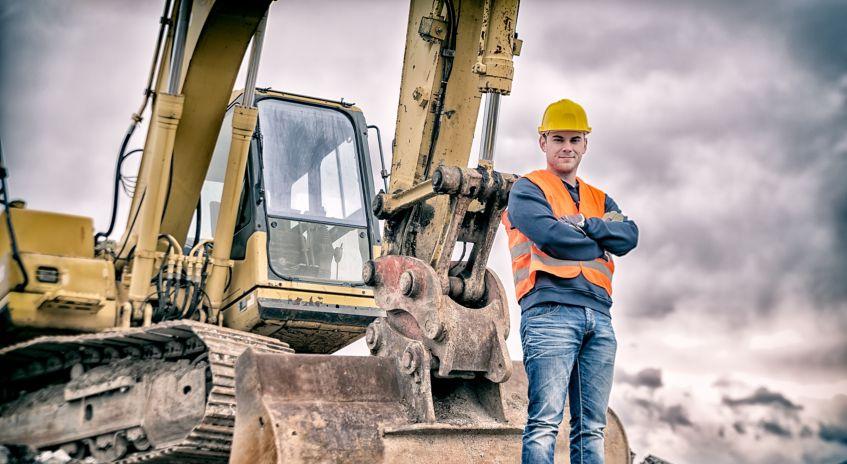 Bilde av en mann som står med hendene i kors og smiler foran en gravemaskin