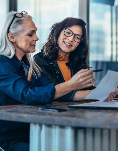Bilde av to smilende damer som ser på et dokument