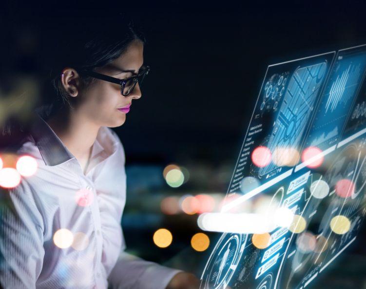 Kvinne med briller ser nøye på en dataskjerm