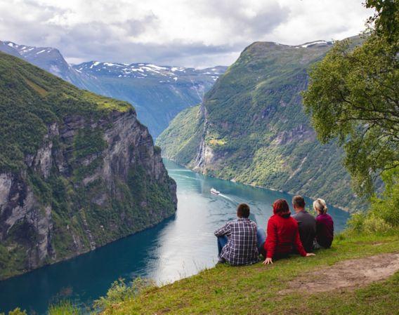 Fire mennesker sitter å ser ut over fjord
