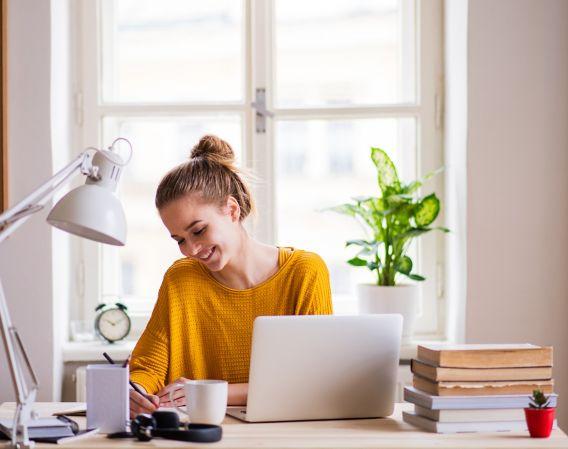 Bilde av en smilende kvinne som jobber på hjemmekontor