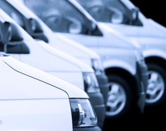 Bilde av mange hvite varebiler som står på rekke og rad