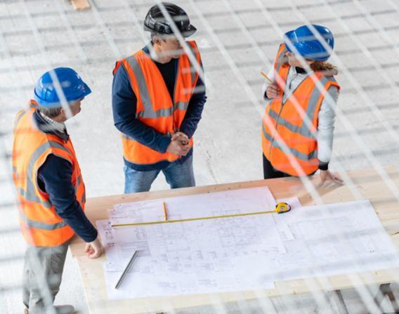 Bilde av tre anleggsarbeidere som ser på tegninger