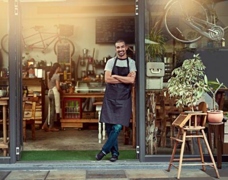 Mann står i forkle foran kaffebar. Foto.