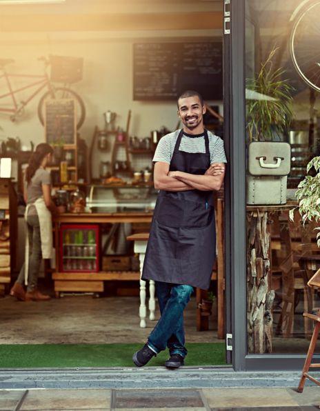 Mann står foran en kaffebar og smiler med armene i kors. Foto.