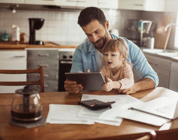 Mann sitter ved kjøkkenbordet med datter og ser på ipad