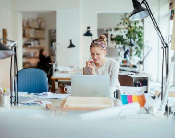 Kvinne sitter ved bord i kontorlandskap og ser på pc