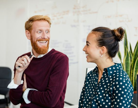 Bilde av en mann med langt ansikt og skjegg, og en dame med prikkete bluse som smiler til hverandre