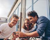Tre unge mennesker sitter ute og ser på en mobil