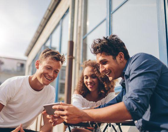 Tre venner ser på mobil og smiler