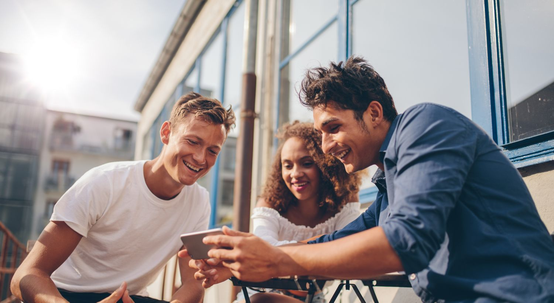 Tre personer som ser på mobiltelefon