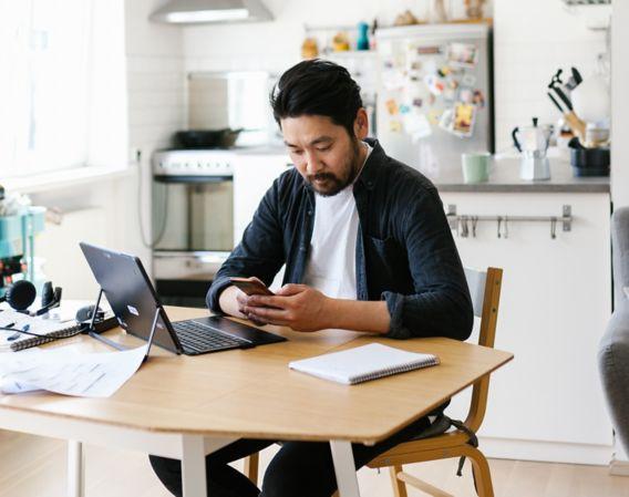 Mann sitter ved kjøkkenbord med pc på bordet og ser på mobilen