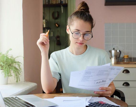 Kvinne sitter ved spisebord på kjøkken og ser på papirer