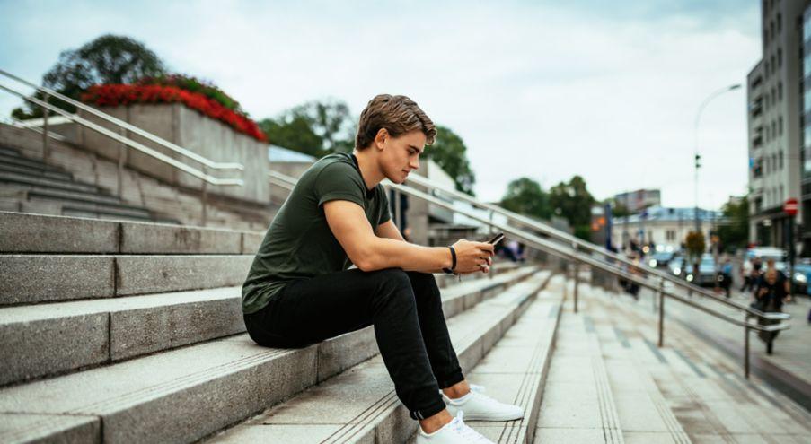 Bilde av gutt som sitter i en trapp med mobilen