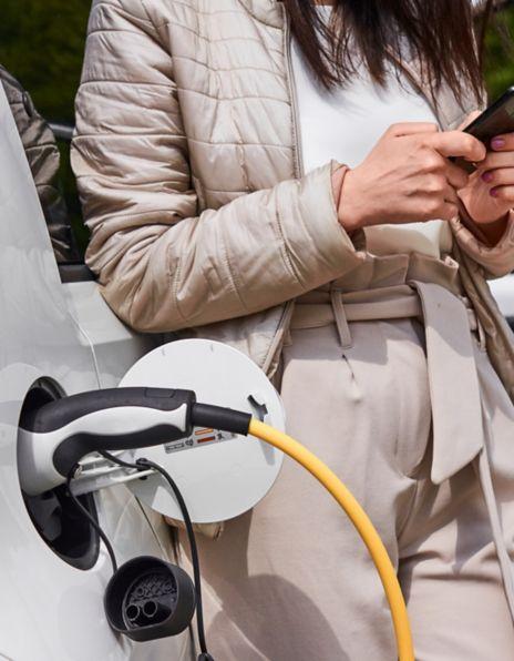 Bilde av en dame som lader en elbil