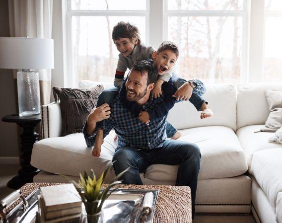Bilde av en far med to sønner i en sofa som leker sammen