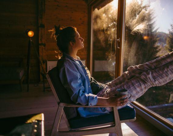 Dame slapper av i en stol på hytta