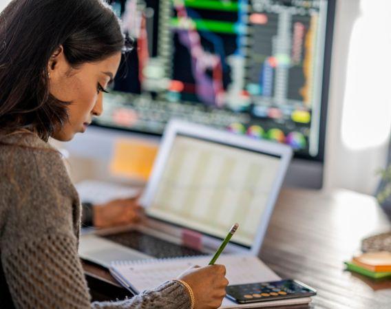 Bilde av en dame som sitter med en PC og bruker penn og tar notater