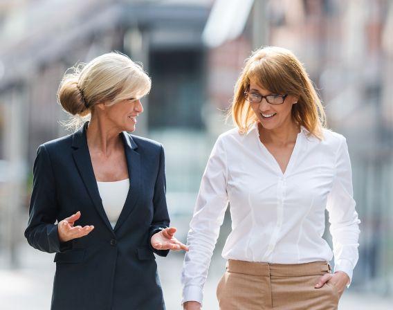 To dresskledde damer går på gaten