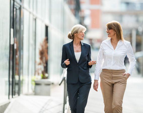To kvinner går langs vei og prater