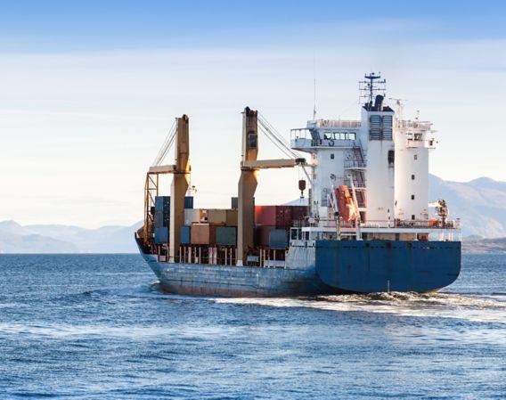 Bilde av et blått lasteskip på havet med en del containere ombord