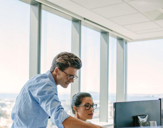 Bilde av en mann og kvinne som ser på en dataskjerm