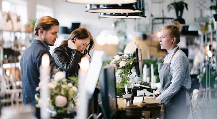 Bilde fra en café hvor en mann og en dame står og prøver å bestemme seg foran disken mens en ansatt venter på ordren.