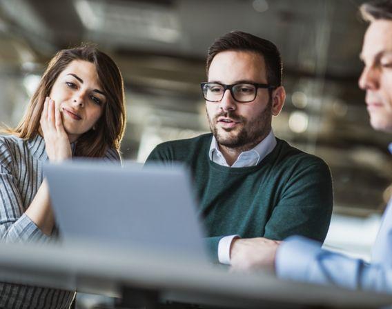 Bilde av tre mennesker som sitter og vurderer et bedriftslån foran en laptop
