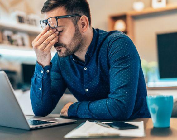 Bilde av stresset mann som sitter foran en laptop