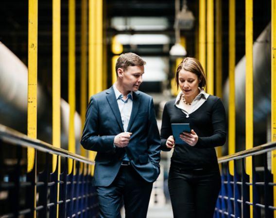 Bilde av to personer som går gjennom en produksjonshall og ser på et nettbrett