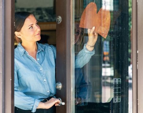 Dame som åpner butikken sin. Foto.