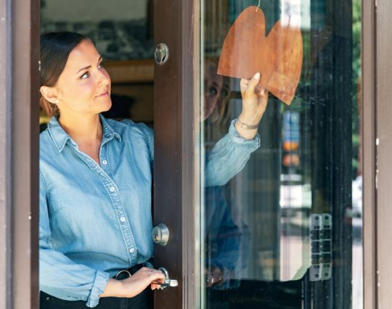 Bilde av kvinne som åpner butikken sin