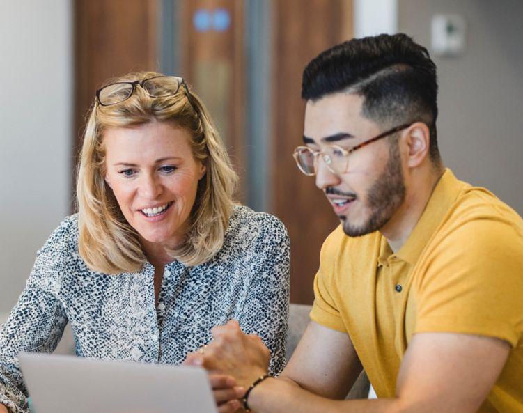 To mennesker diskuterer og ser på en datamaskin