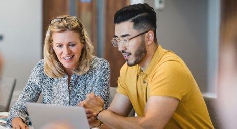En ung dame og ung mann sitter foran en skjerm og deltar på webinar om aksjehandel.