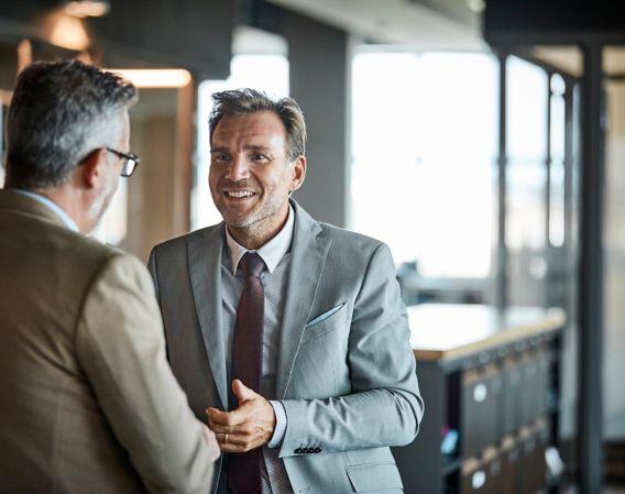 Bilde av to menn med grått hår i dress som prater sammen