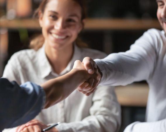 Forretningsmøte der to mennesker  tar hverandre i hånden mens en dame sitter ved siden av og smiler