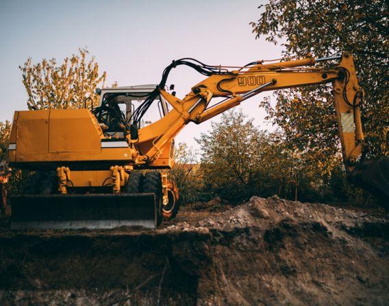 Bilde av en gravemaskin som graver en grøft på høsten