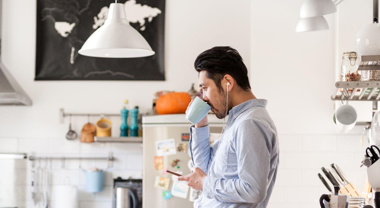 Mann som drikker kaffe og jobber