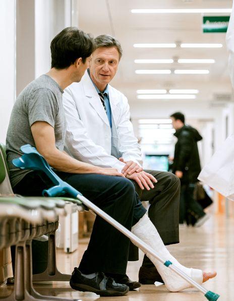 Bilde av en mannlig lege og en mannlig pasient med krykker på sykehus
