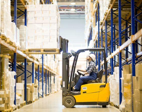 Bilde av en truck med en arbeider som løfter en palle med esker inne på et lager
