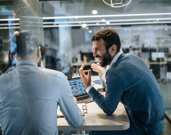 To kollegaer som smiler foran en PC