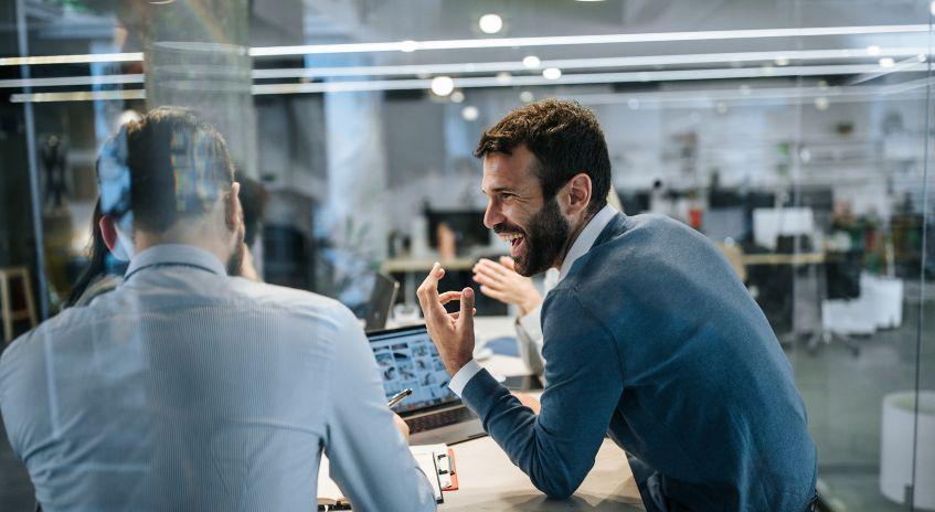 To mannlige kollegaer som smiler til hverandre