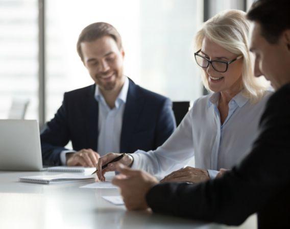 Bilde av tre kolleger som ser på noen ark og smiler