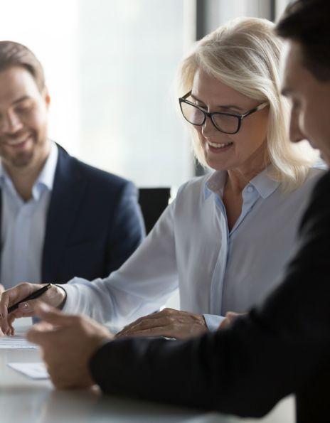 To menn og en kvinne som ser på en avtale. Illustrasjonsfoto MiFID kundeavtale.